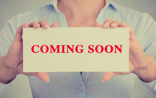 Businesswoman hands holding white card sign with coming soon text message isolated on grey wall office background. Retro instagram style image